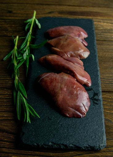 Raw chicken liver on slate board on aged wooden...