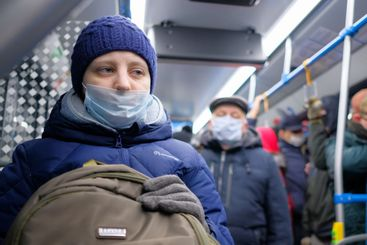 Young woman wearing a surgical protective mask on public...