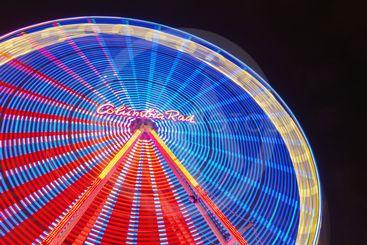 Christmas market with illuminated ferris wheel in...