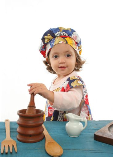 Little girl cooking dressed at a cheff