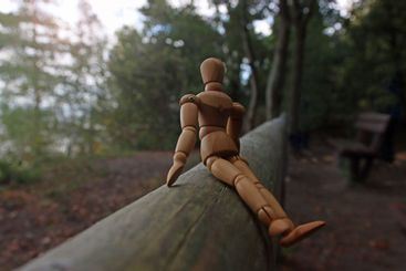 Close up of a wooden mannequin sitting on a beam in the...