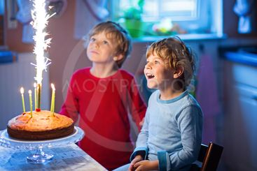 little kid boys twins celebrating birthday and blowing...