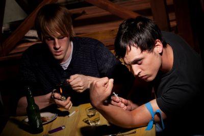 Two men preparing heroin
