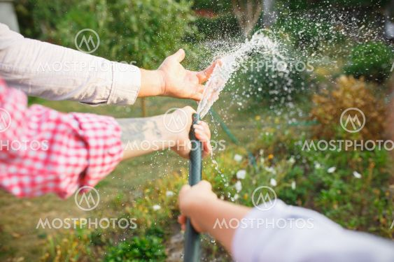 Happy family during watering plants in a garden...