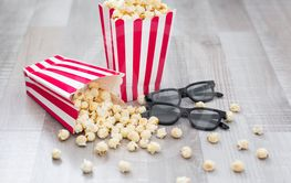 cinema concept - close up of 3d glasses and popcorn in...