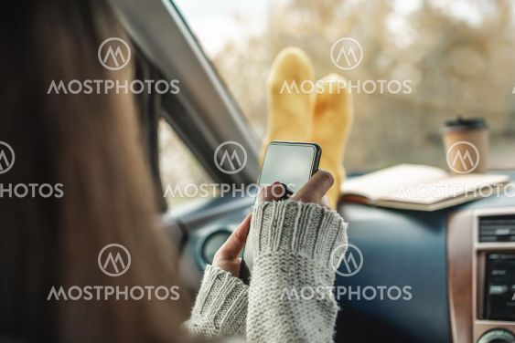 Woman in a car in warm socks is holding a mobile phone...