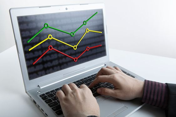 hands of a person working on a computer with graphs