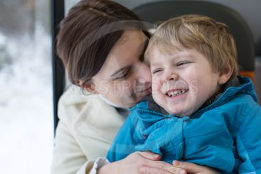 Mother and toddler son having fun in train