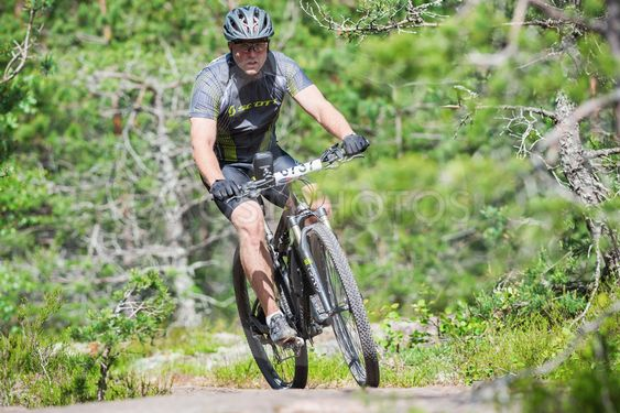 Man on mountain bike out of a curve in the forest at Lida...