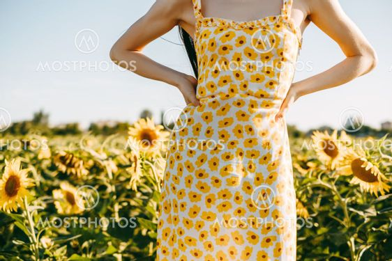 Young caucasian woman in sunflower dress standing in...