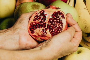 Old hands grabbing a passion fruit over a full of fruits...