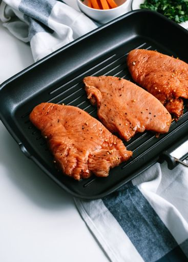 Marinated turkey steak with spices in a black grill pan...