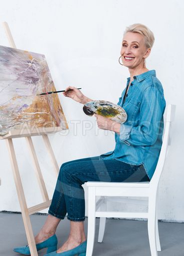 senior woman painting on easel with paintbrush and...