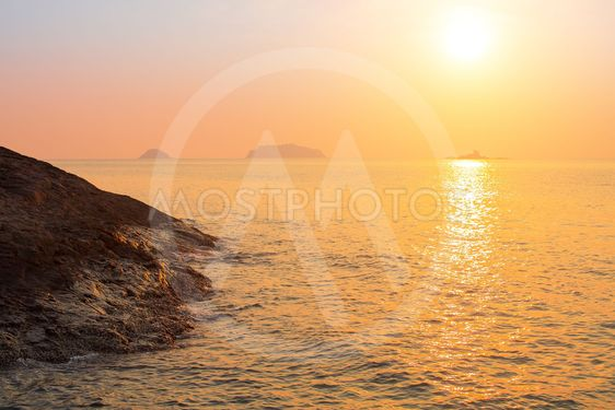 Rocky sea shore against the setting sun.
