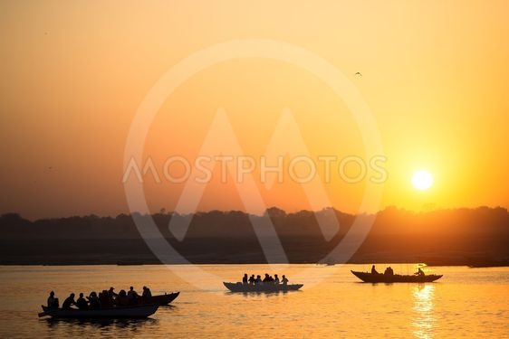 Boat silhouettes with pilgrims during amazing sunset on...