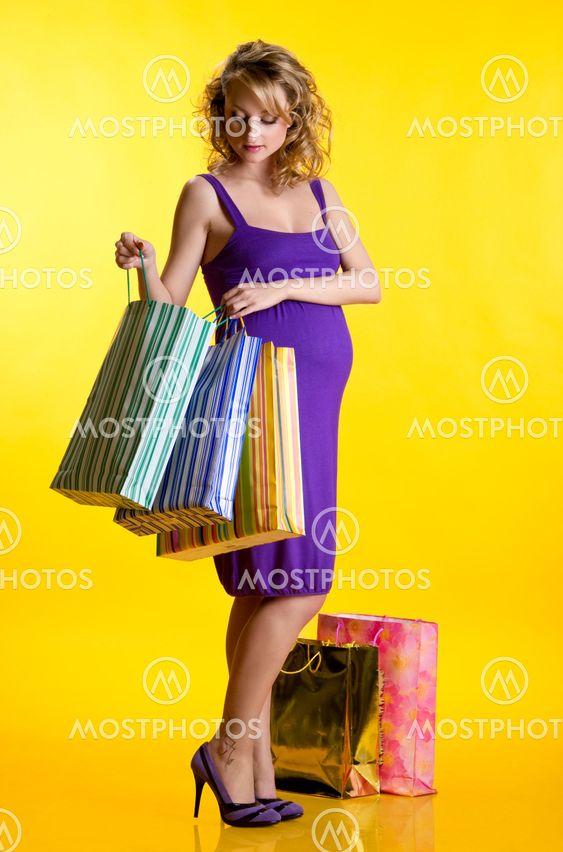 Beautiful pregnant woman looking inside shopping bags