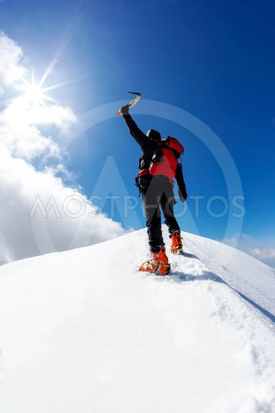 climber reaches the summit of a snowy mountain in winter
