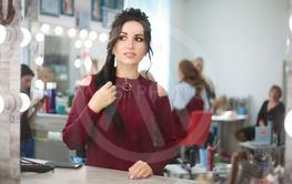 Woman in a beauty salon looks at her reflection in the...