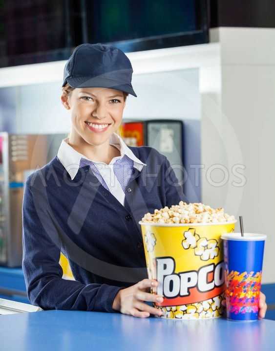 Smiling Worker With Popcorn And Drink At Concession Stand