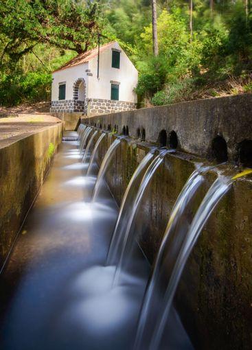 Water pouring in streams into a concrete levada