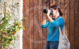 young woman taking photos in traditional mediterranean...