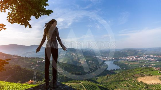 Young woman with blond dreadlocks standing on the edge of...