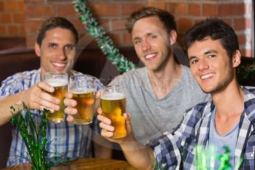 Happy friends toasting with pints of beer on patricks day