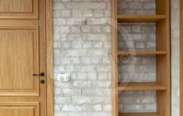 Oak door and bookcase against white brick wall
