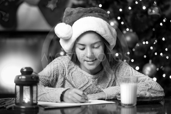 portrait of cute girl writing letter to Santa Claus at...