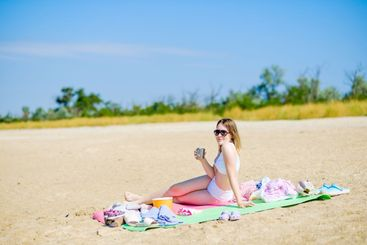 A young girl in a white bathing suit on a sunny day on a...