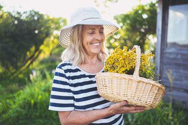 Happy smiling elderly senior woman in straw hat having...
