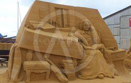 mand læser i bog som er lavet i sand