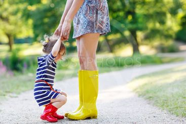 mother and little adorable child girl in rubber boots...