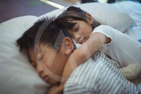 Siblings sleeping on bed in the bed room