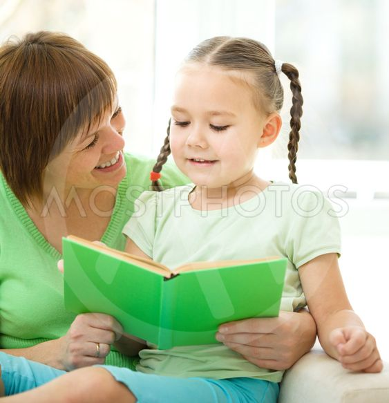 Mother is reading book for her daughter