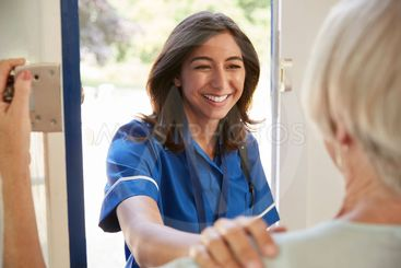 Nurse on home visit greets senior woman, over shoulder view