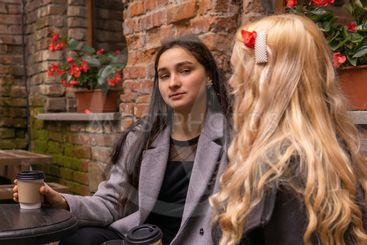 girl in disbelief  listens to her friend on a bench with...