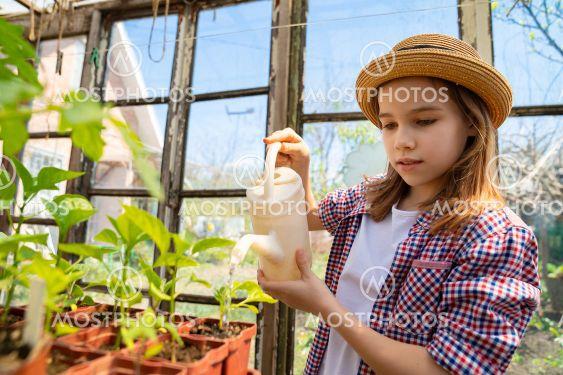 Adorable teen girl kid in hat watering seedlings