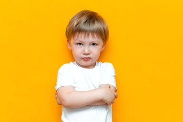 Portrait of angry little boy with arms folded isolated...