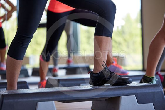 close up of women exercising with steppers in gym