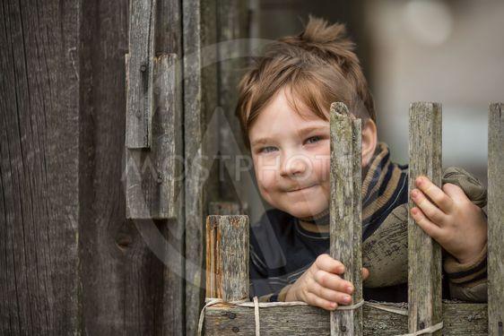 Portrait of little boy near a fence in the village.