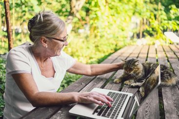 Happy senior old woman with home cat working online with...