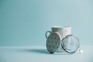 A clean cup of tea over a pastel blue background with...