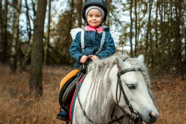 Little girl on a white pony on a background of nature....