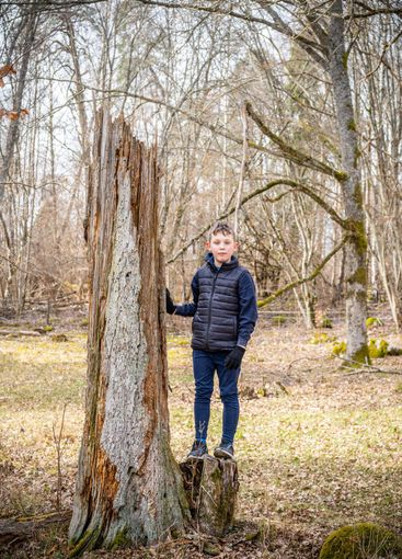 Stadsbarn i naturen bredvid dött träd.