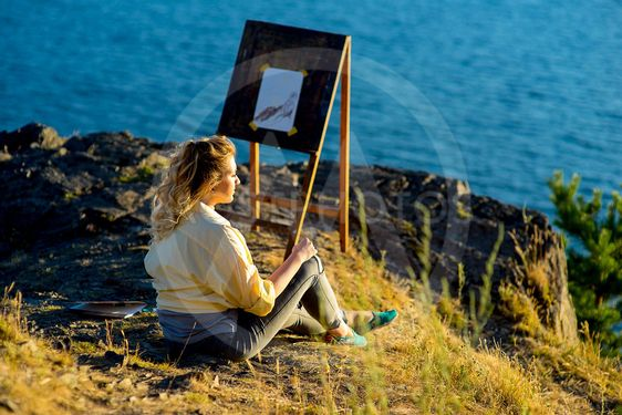 young artist draws a seascape at sunset