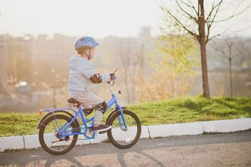 Little boy in helmet rides a bicycle on a sunny day