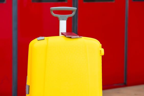 Closeup red passports on yellow luggage at train station