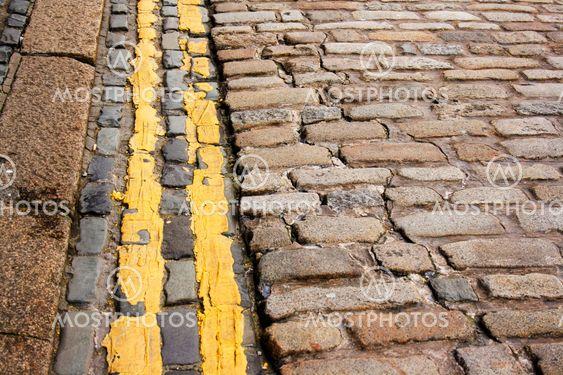 Moderne (ingen parkering) dobbelt gul linjer langs antikke brostensbelagte sten