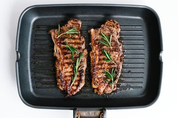 Grilled beef steak with rosemary in black grill pan on...